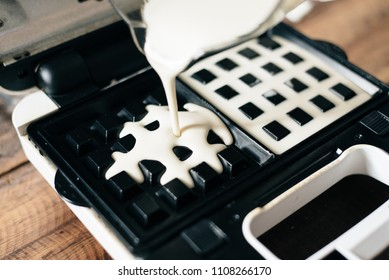 pouring dough on waffle maker. preparing waffle