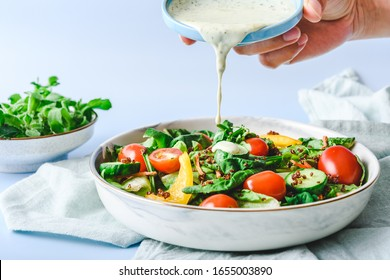 Pouring Dressing on Garden Salad on a light green cloth and light blur background