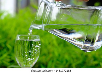 pouring drinking mineral water on counter and green background