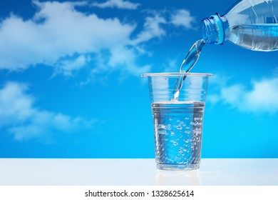 Pouring drinking water from  plastic bottle into  glass, against  blue sky with clouds. Sparkling water with bubbles in  plastic cup. Copy space.