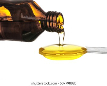 Pouring of fish oil from bottle into spoon, isolated on white