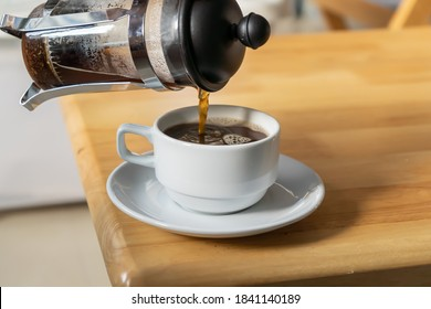 Pouring French press coffee into a cup on a table