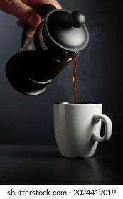 Pouring French press coffee into a cup on a black table.