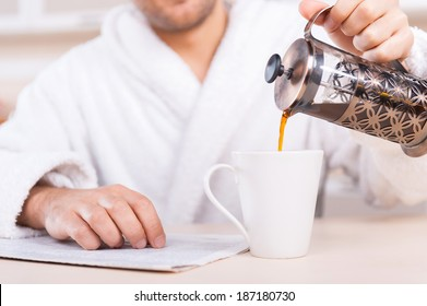 Pouring fresh coffee. Cropped image of man in bathrobe pouring coffee to the cup