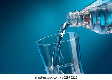 Pouring fresh mineral water from a bottle into a glass, hydration and diet concept
