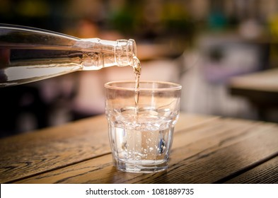 Pouring fresh mineral water into glass from a bottle. Wooden table in a restauran