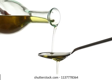 Pouring fresh olive oil into spoon on white background