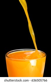 Pouring fresh orange juice into glass on black background