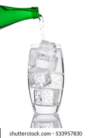 Pouring fresh sparkling water from bottle to glass on white background