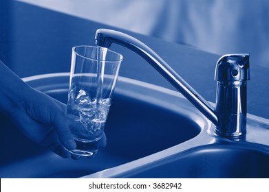 Pouring Fresh Tap Water Into a Glass. Shallow DOF. Focus on Tap.