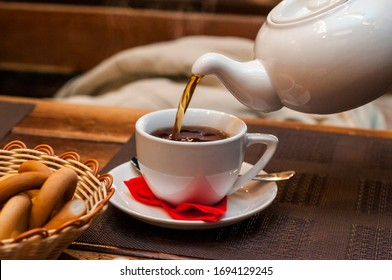 Pouring fresh tea from porcelain tea kettle into white cup. Focus on tea stream, shallow depth of field.