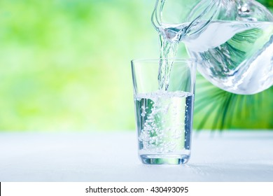 Pouring fresh water in the glass on the background of nature.
