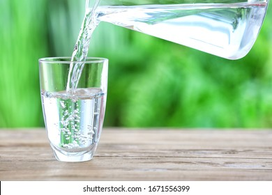 Pouring of fresh water into glass on table outdoors