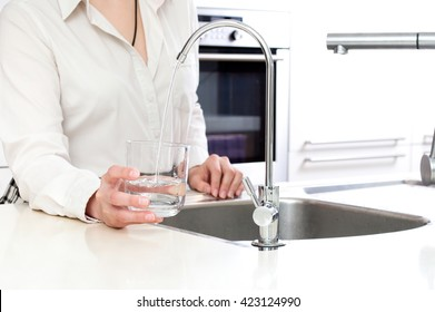 Pouring fresh water from ozone filter into the glass by woman in kitchen