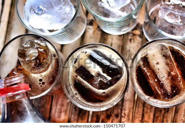 Pouring a glass of cola with ice cubes
