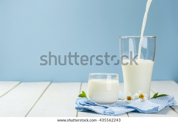 Pouring a glass of milk on a white wooden table on a blue background, nutritious and healthy dairy products concept