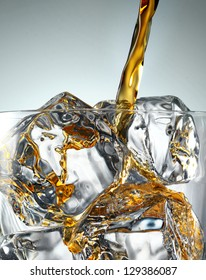 Pouring Glass of scotch whiskey and ice