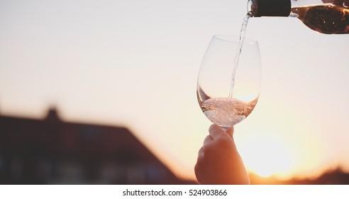 Gießen eines Glases Weißwein gegen den Sonnenuntergang. Entspannen Sie am gemütlichen Abend auf der Terrasse. Nicht erkennbare weibliche Hand, die eine Winde auf dem Innenhof hält. Kinematikaufnahme. Lens Flare.