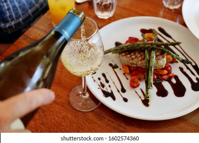 Pouring Glass of White Wine with Rare Tuna Steak in Background