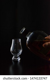 Pouring a glencairn glass of Kentucky straight bourbon whiskey in front of a black background. The glass reflections shine of the black wood surface. Portrait orientation with copy space.