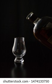 Pouring a glencairn glass of Kentucky straight bourbon whiskey in front of a black background. The glass reflections shine of the black wood surface.