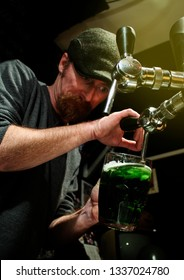 Pouring green beer in glass jug by bartender in Irish pub or some other beer temple aka beer house