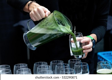 pouring green juice from a pitcher into glass