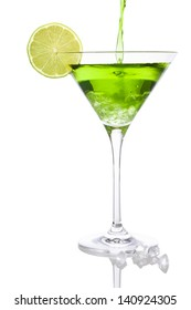Pouring a green liquid into a Martini glass with lime slice and crushed ice, isolated on white background