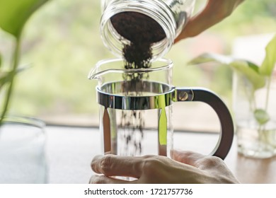 Pouring ground coffee into the French press coffee maker. Focus on the glass jug.