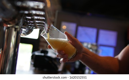 Pouring a Hazy Beer into a Glass in a Brewery Taproom