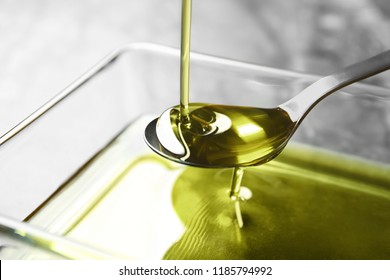 Pouring hemp oil into spoon over glass bowl, closeup