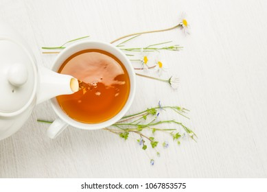 pouring herbal tea into cup on white table