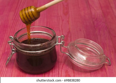pouring  honey in glass pot on pink wooden table