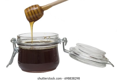 pouring  honey in glass pot on white background