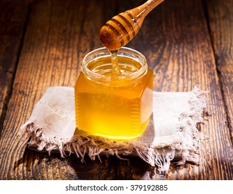 pouring honey into jar on wooden table