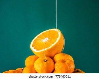 Pouring honey on fresh halves oranges on top of fresh plie of oranges with copy space teal color background