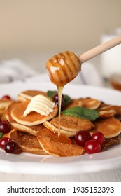 Pouring honey onto cereal pancakes with cranberries at white wooden table, closeup