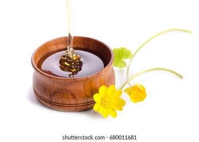 pouring honey in the wooden bowl with yellow flowers isolated on white background