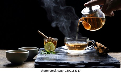 Pouring hot aromatic herbal tea from teapot into glass teacup set with steam and various herbs on black stone plate with wooden table floor in dark background, selective focus