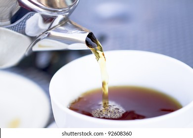 Pouring hot black tea from restaurant style cattle. Selective focused on kettle and poured tea.
