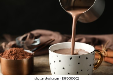Pouring hot cocoa drink into cup on wooden table