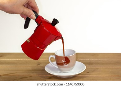 Pouring a hot expresso coffee into a glass