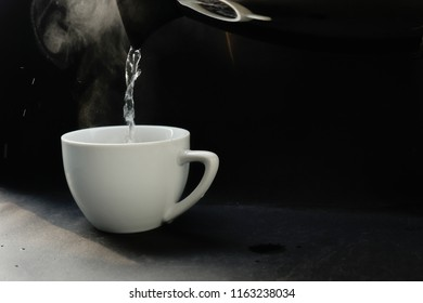 Pouring hot water in americano coffee cup in morning. Americano maker and black texture.