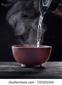 Pouring hot water into into a bowl on a black background