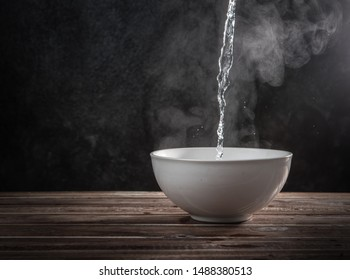Pouring hot water into into a ceramic bowl against black cement wall
