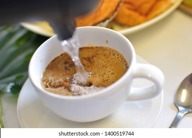 Pouring hot water from kettle into white coffee cup of instant coffee, easy and convenient for drink caffeine, preparing for refreshing concept