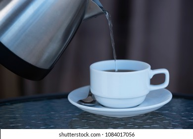 Pouring hot water from a kettle to make hot coffee