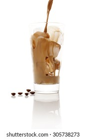 Pouring ice coffee into glass with ice cubes isolated on white background. Culinary coffee drinking.
