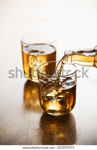 Pouring ice tea in glass with ice cubes.