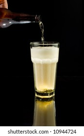 Pouring an ice-cold beer into a glass, isolated against black with reflection